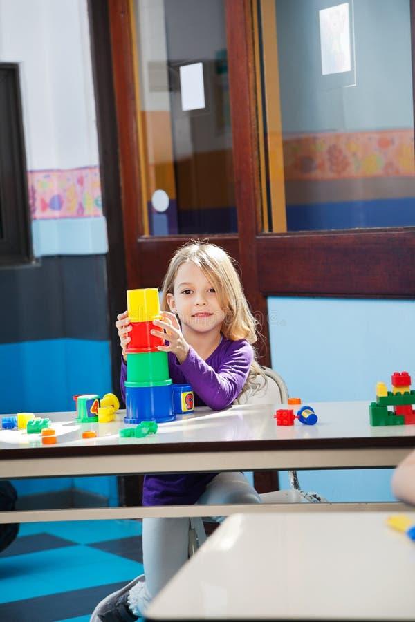 Mädchen, das mit Spielwaren im Kindergarten spielt stockbilder