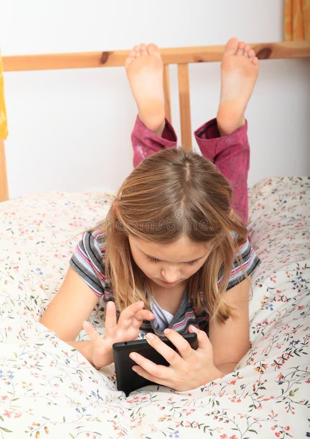 Mädchen, das mit Tablette spielt lizenzfreie stockfotografie