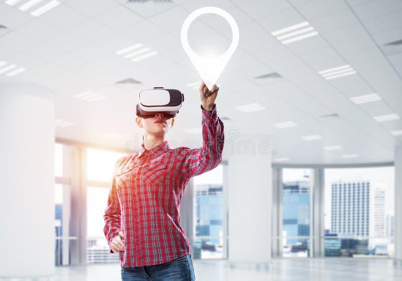 Mädchen, das mit VR-Gerät an der Platte aufpasst und an ihr arbeitet Mischm stockbilder