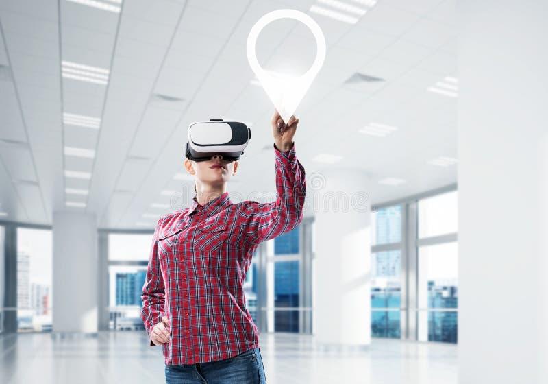 Mädchen, das mit VR-Gerät an der Platte aufpasst und an ihr arbeitet Mischm stockfotografie
