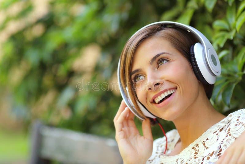 Mädchen, das Musik mit Kopfhörern in einem Park hört lizenzfreies stockfoto