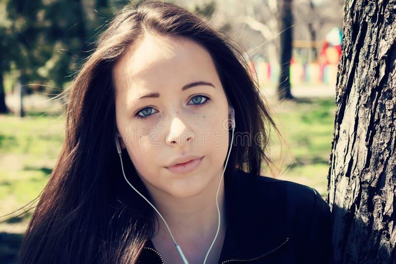 Mädchen, das Musik mit Kopfhörern in einem Park hört lizenzfreie stockfotos