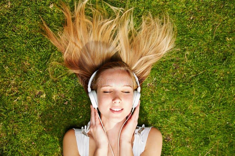 Mädchen, das Musik strömt im Sommer hört stockfoto