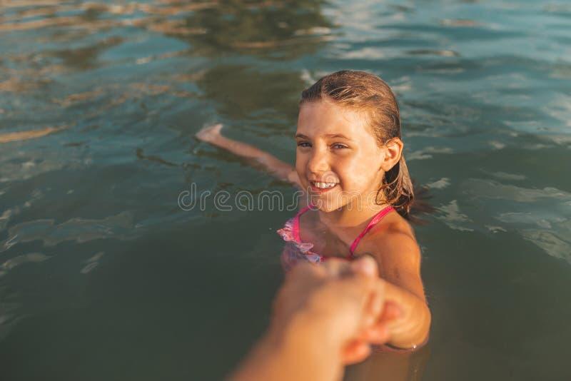 Mädchen, das Mutter ` s Hand beim Gehen durch das Wasser zieht lizenzfreie stockfotografie