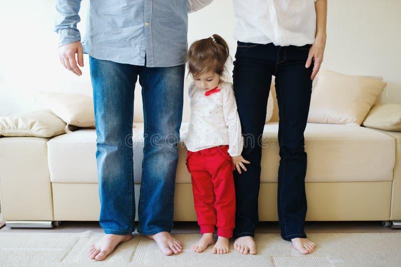Mädchen, das Mutter und Vati für Beine umarmt lizenzfreie stockfotos