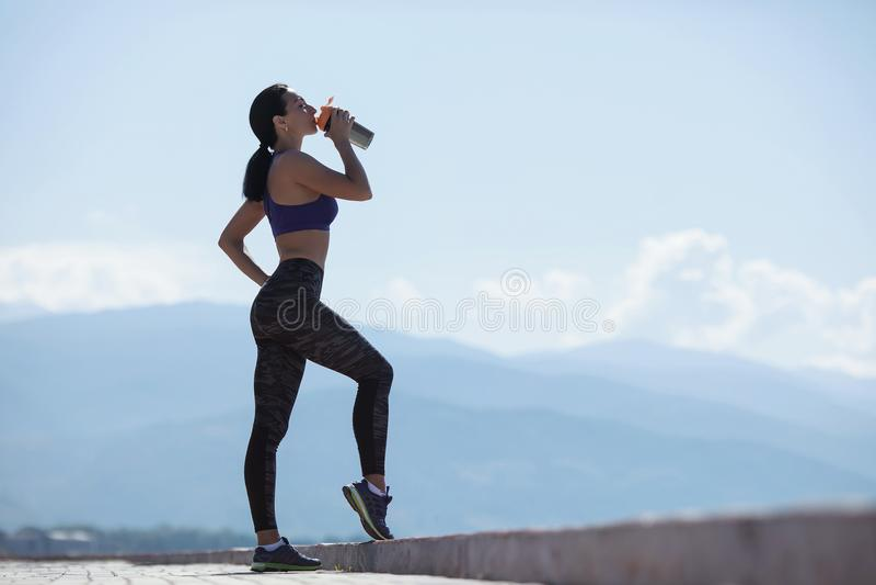 Mädchen, das nachdem dem Trainieren, Getränkwasser von den Flaschen stillsteht stockbild
