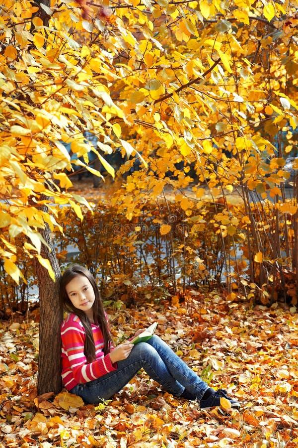 Mädchen, das nahe Baum sitzt und ein Buch liest stockbilder