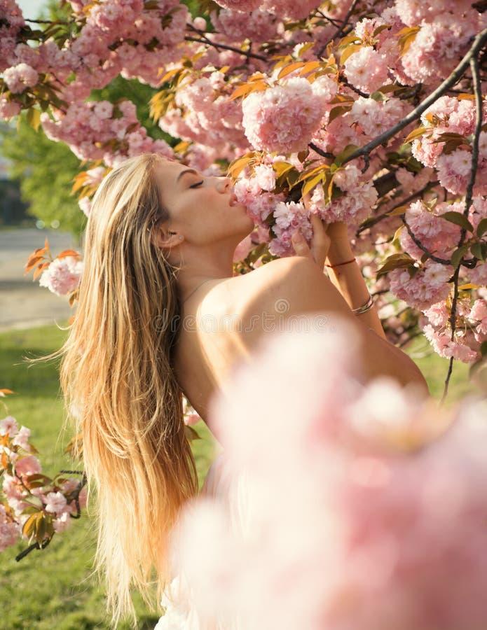 Mädchen, das nahe bei blühendem rosa Baum aufwirft Nackte auf blumigem Hintergrund, Einheit mit Naturkonzept vollkommen lizenzfreie stockbilder
