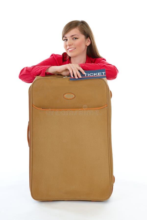 Mädchen, das nahe einem Koffer sitzt lizenzfreies stockfoto