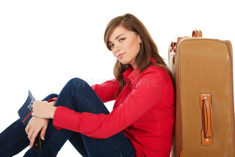 Mädchen, das nahe einem Koffer sitzt stockfoto