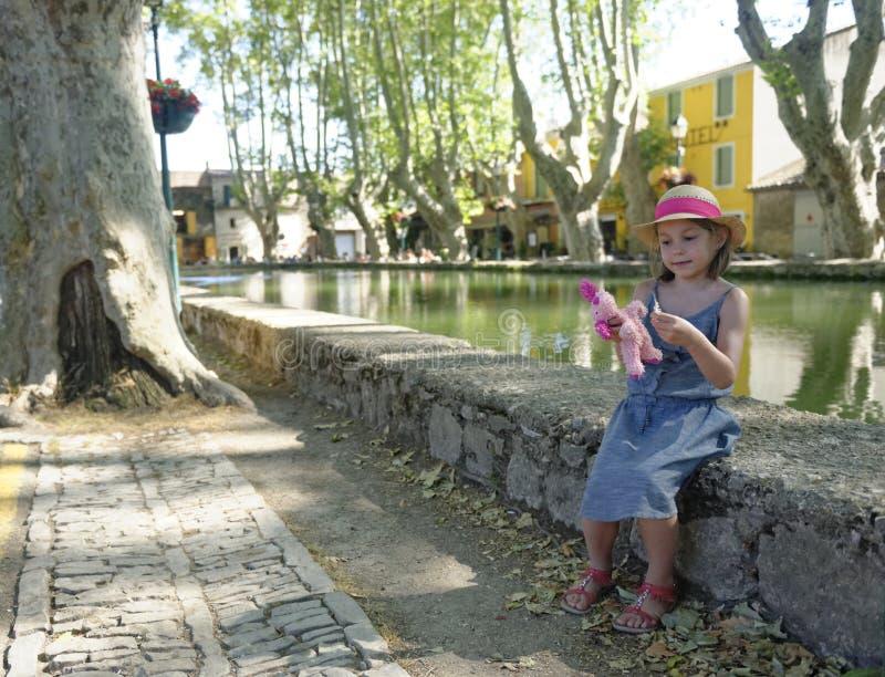 Mädchen, das neben Teich sitzt stockfoto