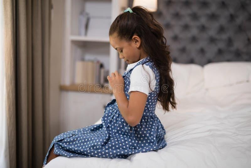 Mädchen, das oben beim auf Bett zu Hause sitzen ankleidet lizenzfreie stockfotografie
