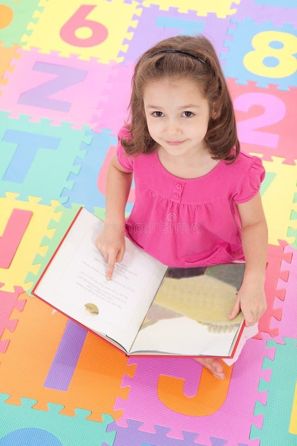 Mädchen, das oben vom Lesebuch auf Alphabetmatte schaut lizenzfreie stockbilder