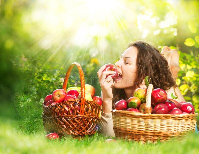 Mädchen, das organischen Apple im Obstgarten isst lizenzfreie stockbilder