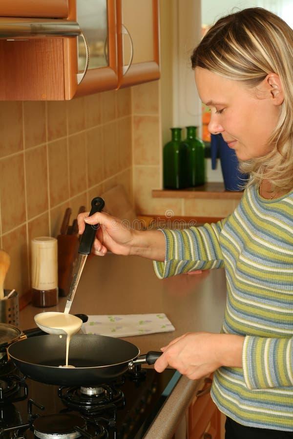 Mädchen, das Pfannkuchen zubereitet. stockbild