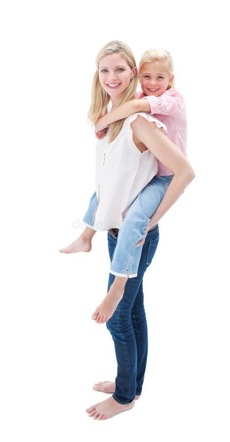 Mädchen, das piggyback Fahrt mit ihrer Mutter genießt stockfotos