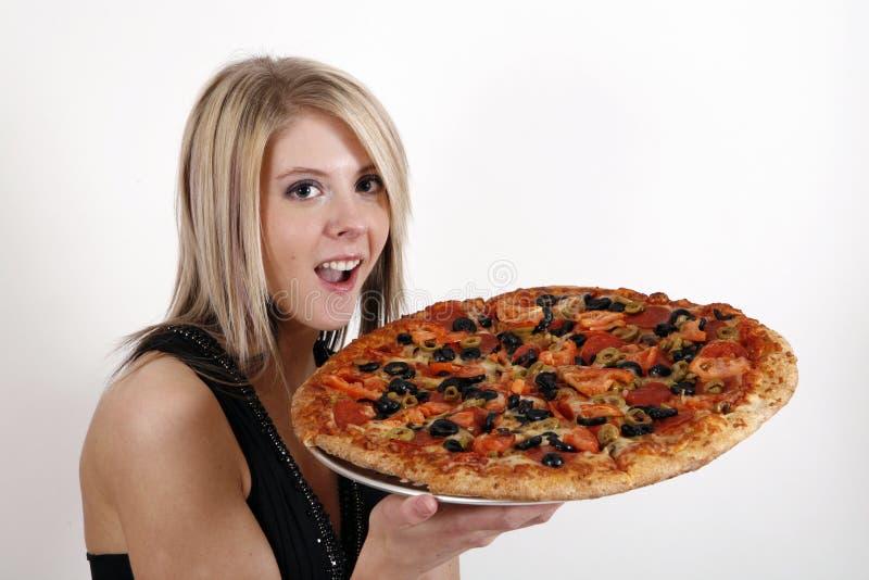 Mädchen, das Pizza zeigt lizenzfreie stockfotografie