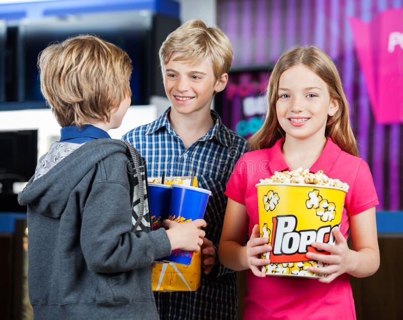 Mädchen, das Popcorn während Brüder sprechen an hält lizenzfreies stockfoto