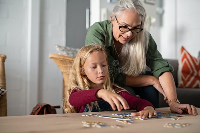 Mädchen, das Puzzlen mit Großmutter tut stockfotografie