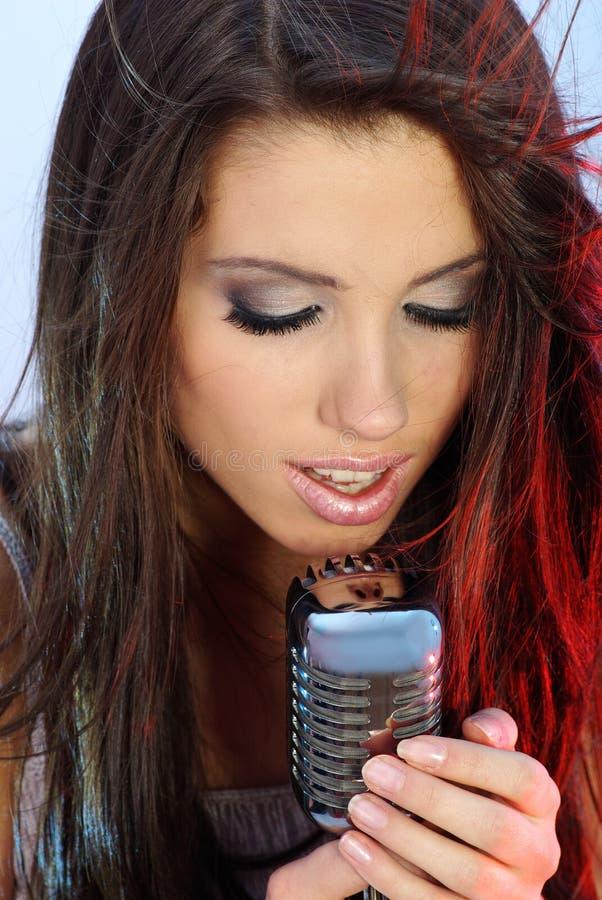 Mädchen, das in Retro- mic singt stockfotografie