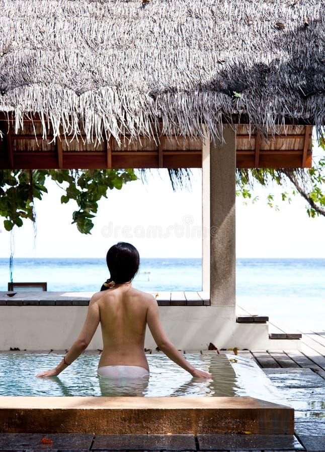 Mädchen, das in Richtung zum Meer im Swimmingpool überwacht lizenzfreie stockfotografie