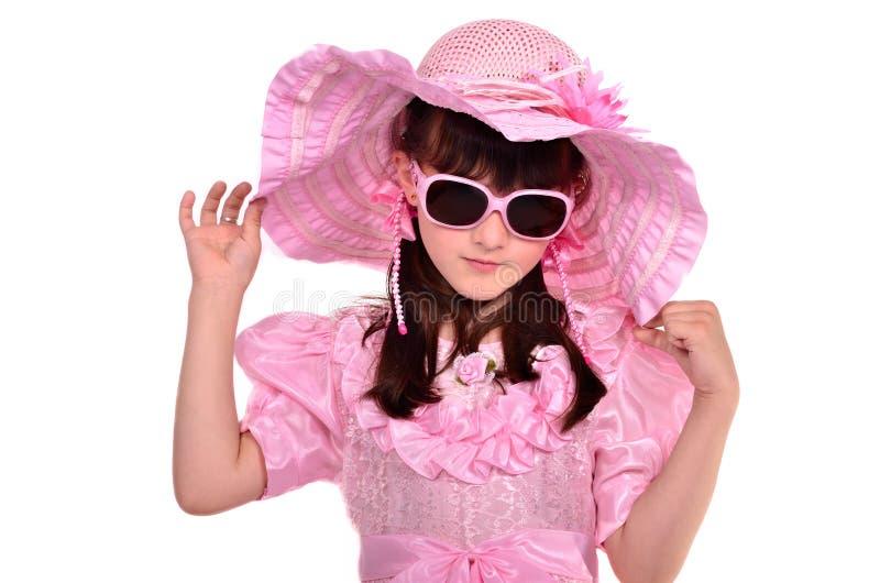 Mädchen, das rosafarbenes Kleid, Hut und Gläser trägt lizenzfreie stockfotografie