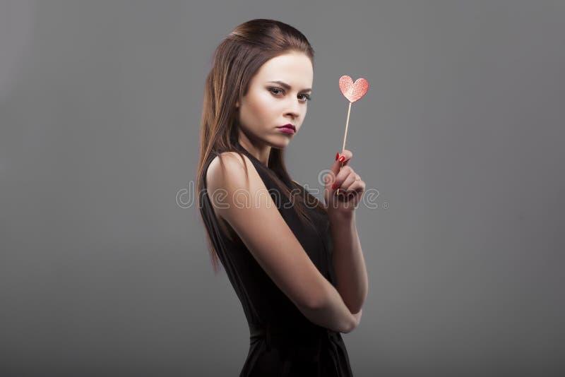 Mädchen, das rotes Papierherz, lokalisierten, grauen Hintergrund hält junge Mode mit ernster Gesichtsgefühlfrau lizenzfreies stockfoto