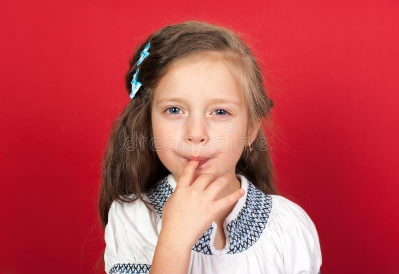 Mädchen, das süßes Lebensmittel vom Finger isst lizenzfreie stockfotografie