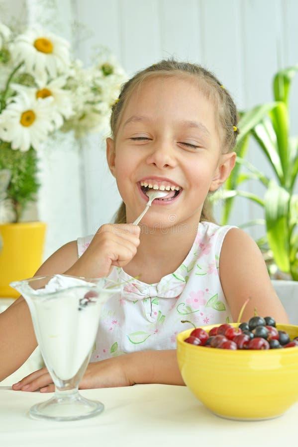 Mädchen, das Süßspeise mit Beeren isst stockfotos