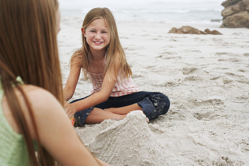 Mädchen, das Sandburg mit Schwester At Beach macht lizenzfreie stockfotos