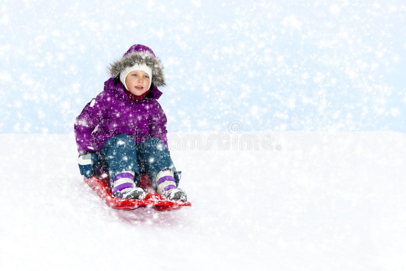 Mädchen, das in Schnee schiebt stockfotos