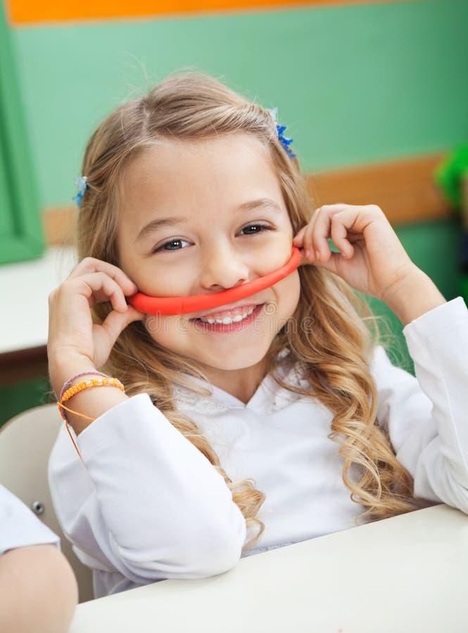 Mädchen, das Schnurrbart hergestellt von Clay In Preschool hält lizenzfreie stockfotos