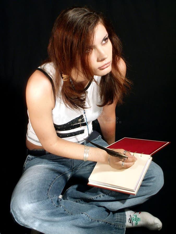 Mädchen, das, schreibend in ein Tagebuch träumt stockbild