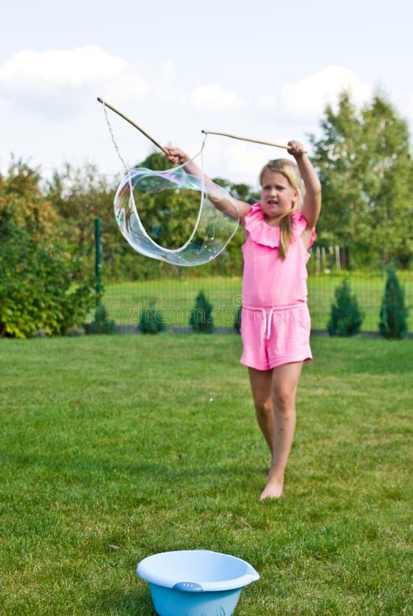 Mädchen, das Seifenblasen im Hausgarten macht stockbilder