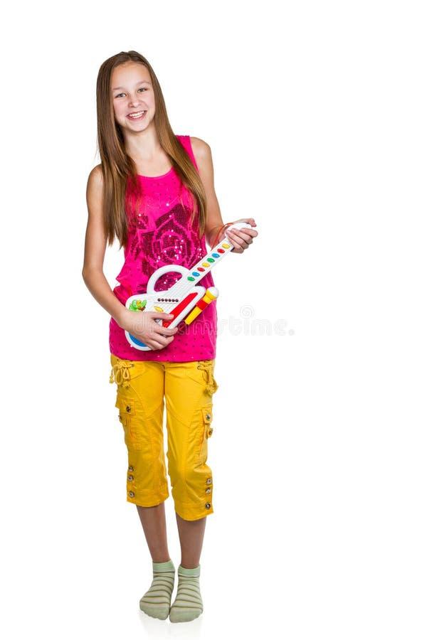 Mädchen, das seine Spielzeuggitarre spielt lizenzfreie stockfotos