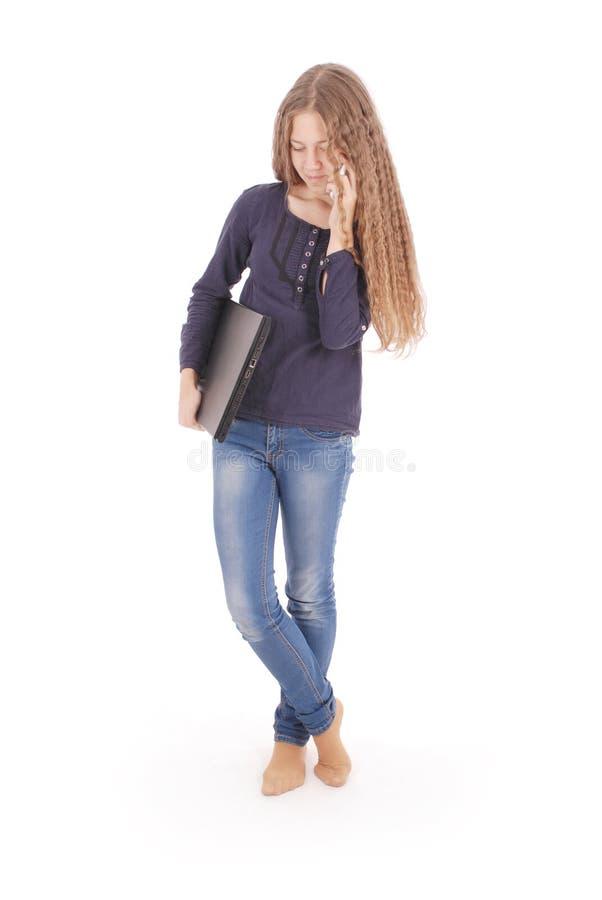 Mädchen, das seitlich auf dem Boden mit Laptop und Smartphone liegt stockfotografie