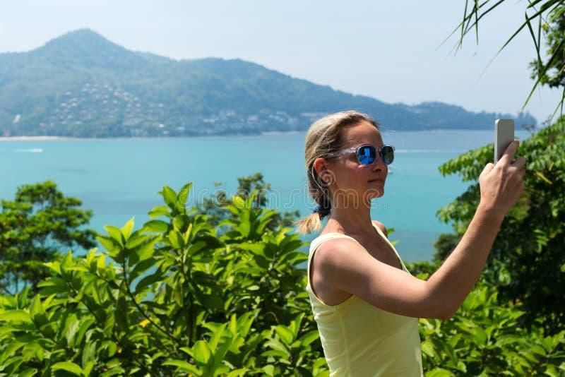 Mädchen, das selfie auf tropischem Strand tut stockbild
