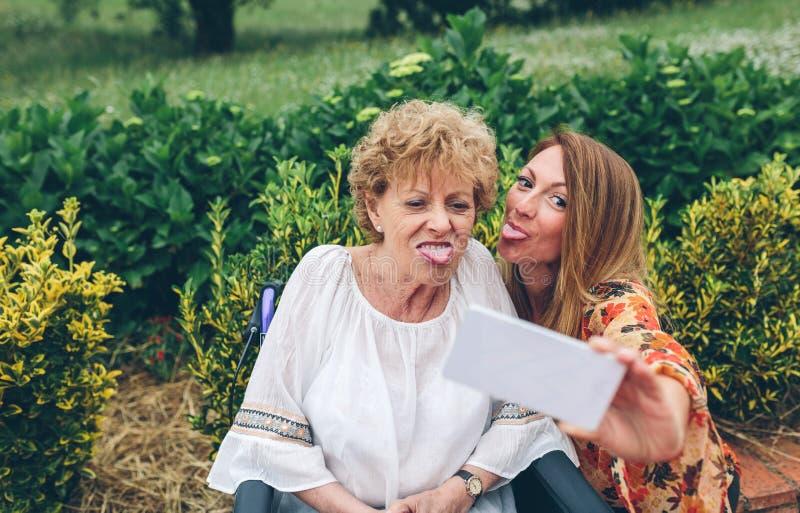 Mädchen, das selfie mit ihrer Mutter im Rollstuhl nimmt lizenzfreie stockbilder