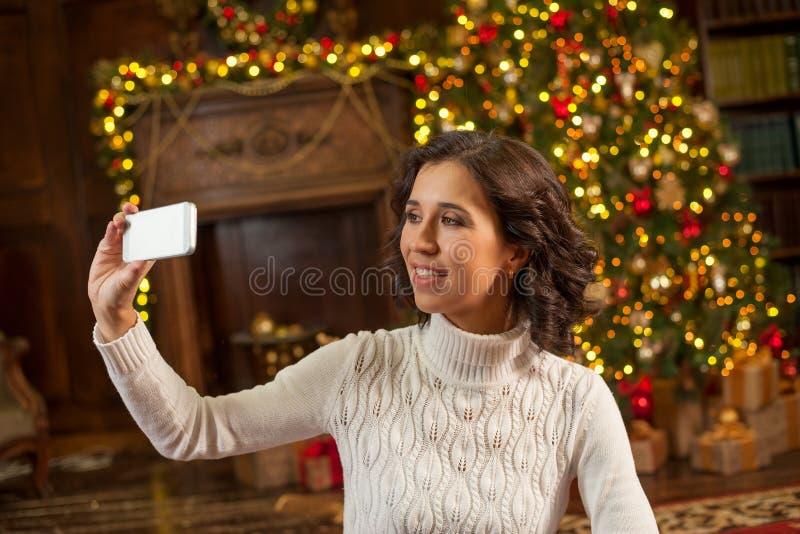 Mädchen, das selfie mit Weihnachtsbaum macht lizenzfreie stockfotografie