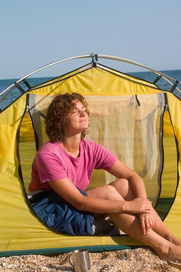 Mädchen, das sich morgens nahe vom Zelt bräunt lizenzfreies stockbild
