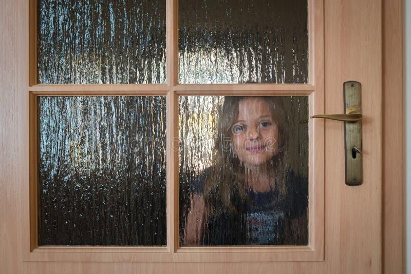 Mädchen, das sich zu Hause hinter Türen versteckt stockfotos