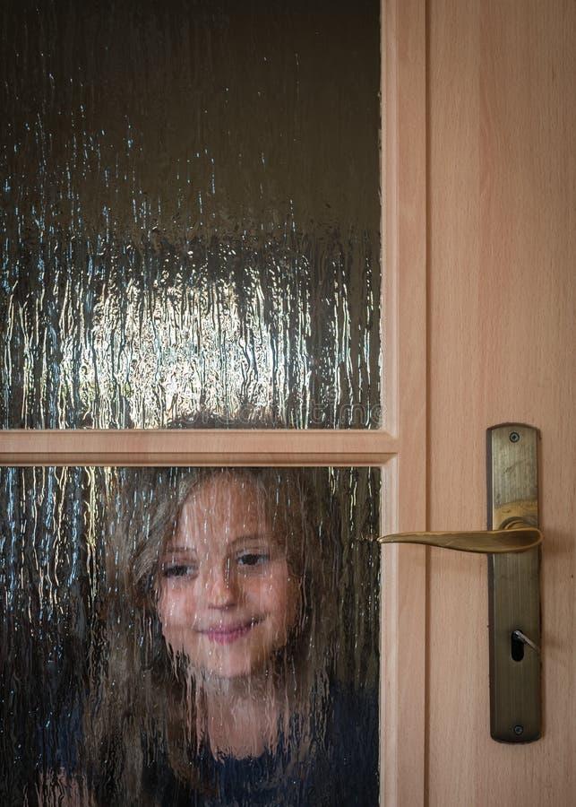 Mädchen, das sich zu Hause hinter Türen versteckt lizenzfreies stockfoto