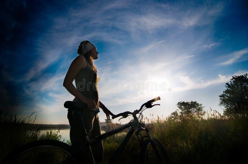 Mädchen, das am Sonnenaufgang radfährt lizenzfreie stockbilder