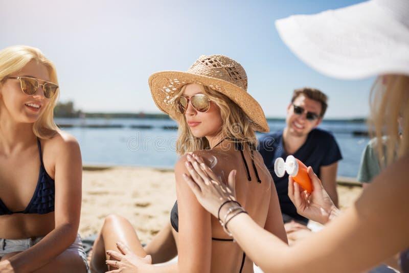 Mädchen, das Sonnencreme auf ihrem Freund aufträgt lizenzfreies stockfoto