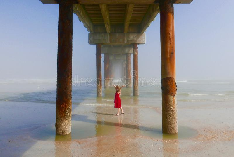 Mädchen, das Sonnenlichtfarben unter einem Ozeanpier genießt lizenzfreie stockfotografie