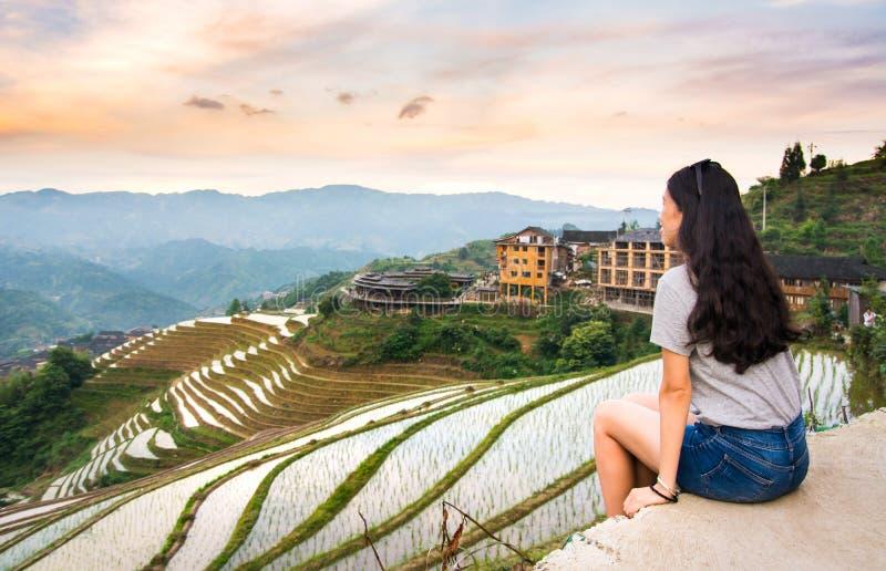 Mädchen, das Sonnenuntergang an terassenförmig angelegtem Reisfeld in Longji, China genießt stockfoto