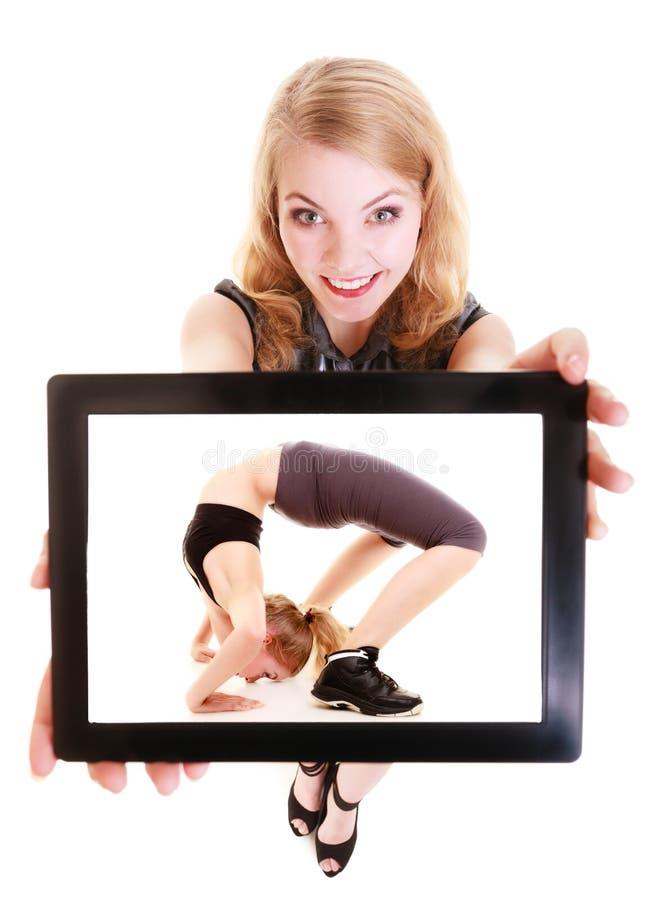 Mädchen, das Tablette mit geeigneter Frau der Eignung zeigt sport lizenzfreies stockfoto