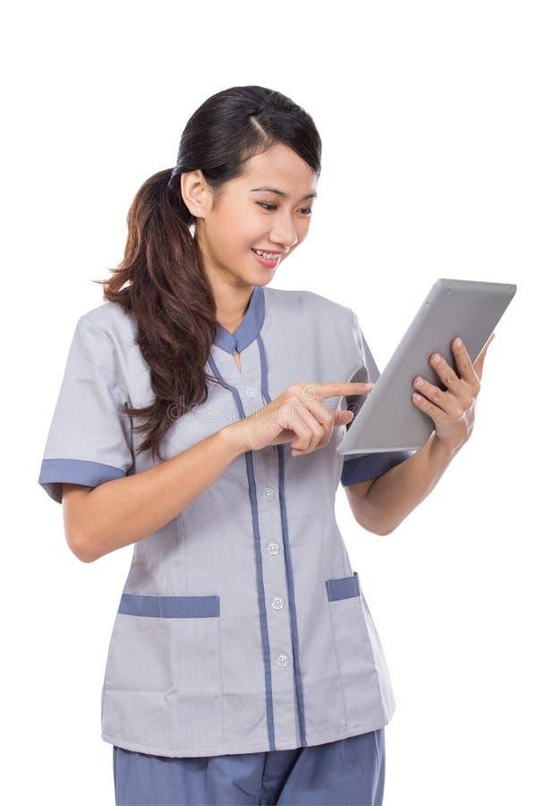 Mädchen, das Tablettennotenauflage verwendet stockbilder