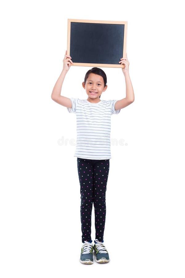 Mädchen, das Tafel und Lächeln über Weiß hält lizenzfreie stockfotos