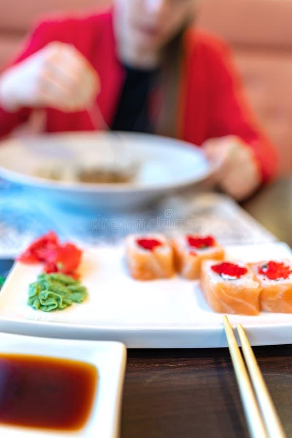 Mädchen, das Teigwaren und Sushi, Unschärfe isst Ohne ein Gesicht Mittagessen, Mahlzeit im Restaurant vertikal rote Kleidung, Sus lizenzfreie stockfotos